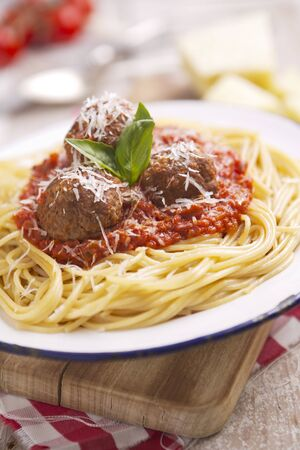 A plate with spaghetti with meatballs, topped with some grated parmesan cheese and basil.