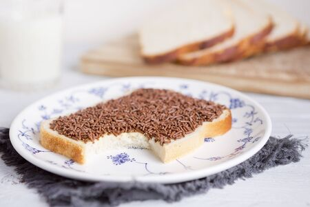 A sandwich with chocolate sprinkles or a 'boterham met hagelslag', Dutch traditional food. 免版税图像
