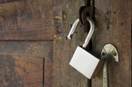 tocar la puerta: desbloqueo de candado en la puerta de madera Foto de archivo