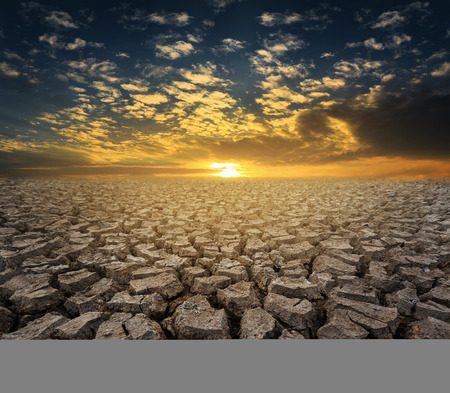 barrenness: Dramatic sunset over cracked earth, global warming.