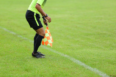 offside: Assistant referees signalling with the flag on the sideline during a soccer match