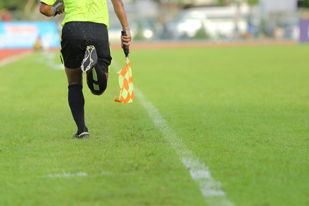 arbitros: Assistant referees signalling with the flag on the sideline during a soccer match