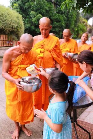 limosna: Chonburi, Tailandia - 18 de octubre de 2015: ofertas de comida budistas dan a un monje budista en la mañana en Nuchanard carretera del pueblo de Tailandia