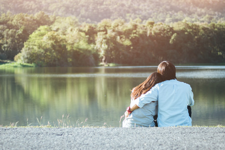 Valentine couple sit at riverside in garden while sunset. Stock Photo