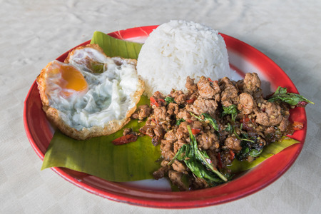Stir fried Thai basil with minced pork and a fried egg in tray.