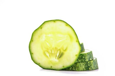 toxins: Cucumber, cut into pieces stacked on white background. Stock Photo