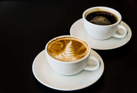 americano: Latte, Americano, leaves and put the right focus on the glass front of a black backdrop.