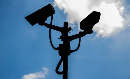close circuit camera: CCTV cameras silhouettes background sky and clouds.