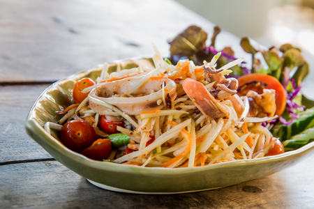 poor light: Thailand Papaya Salad Style Add mussels, squid and octopus focus placed on the wooden floor. The background is blurred and poor light.