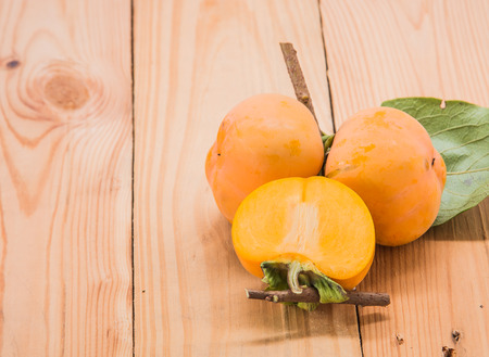 half ball: Three fresh persimmon fruit Full ball and cut in half Placed right on the wooden floor Focus Persimmon.