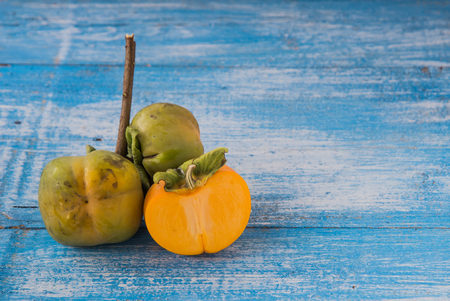 half ball: Fresh ripe persimmon is a full ball and cut in half. Place the left side of the blue and white on a wooden floor. Focus Persimmon. Stock Photo