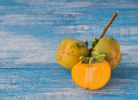 half ball: Fresh ripe persimmon is a full ball and cut in half. Place the timber on the ground, blue and white. Focus Persimmon. Stock Photo