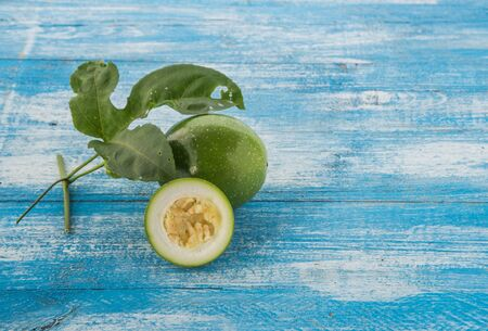 half ball: Fresh green fruit is inedible, full ball and cut in half. Place the timber on a background of blue and white. Passion Fruit Focus. Stock Photo