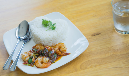 poor light: Shrimp Fried Rice Thailand Style. In white plate placed on a wooden table, focus on shrimp. The background is blurred and poor light.