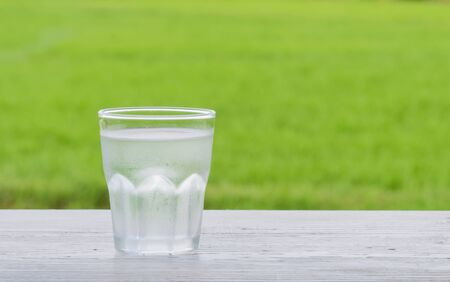 poor light: Cold water in a glass Place the left side on a wooden white. Behind the green fields blur and poor light.