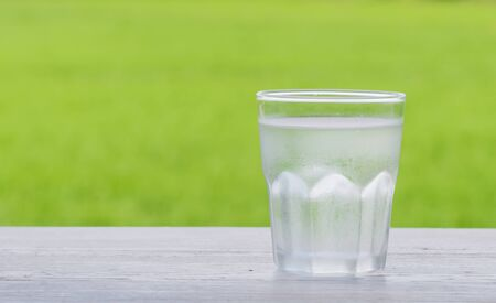 poor light: Cold water in a glass Placed right on the white wood. Behind the green fields blur and poor light.