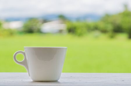 poor light: Fresh coffee in a glass left on the floor, white wood. Behind the green fields blur and poor light. Stock Photo