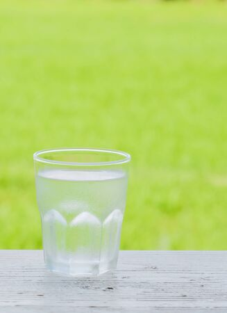 poor light: Cold water in a glass Taken vertically placed left on the floor white wood. Behind the green fields blur and poor light. Stock Photo