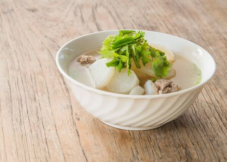 poor light: Pork soup with radish laying on a wooden background blur and poor light.