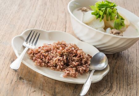 poor light: Rice berries and radish soup Pork placed on a wooden background blur and poor light.