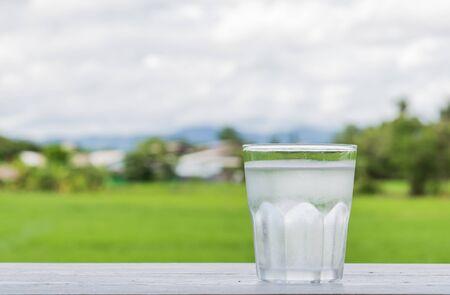 frio: El agua fría en un vaso colocado justo en la madera blanca. Detrás de los campos y el cielo es borrosa luz y pobres.