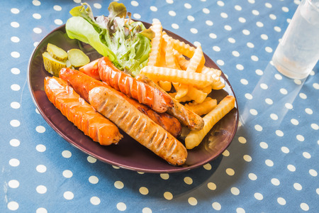 poor light: Sausage and French fries fried in brown plate placed on a blue and white striped fabric. Focus sausages The background is blurred and poor light.