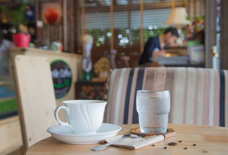 eagerly: Glass of water and coffee.Placed on a wooden table behind blur. Stock Photo