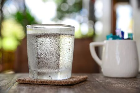 poor light: Water in glass placed on a wooden floor.background blur and poor light,focus on glass.