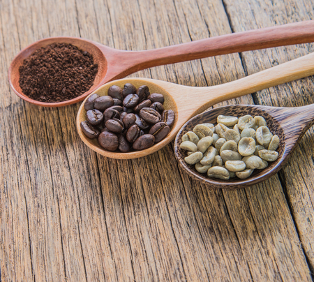 Fresh coffee beans,roasted coffee,ground coffee in wooden spoon.place on wooden floor.focus roast coffee.
