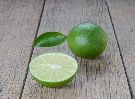 half ball: Green lemon cut half,Full ball placed on wooden floor. Stock Photo