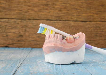 upper floor: Denture mold,false teeth,old toothbrushes placed on wooden floor. Stock Photo