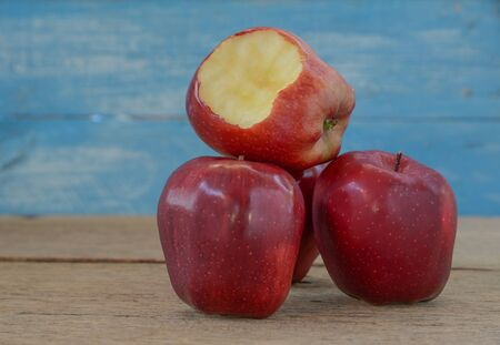 radicals: Tree Red Apples placed on wooden floor.Focus bite the apple. Stock Photo