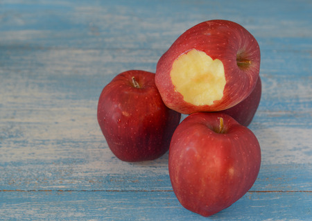 scurvy: Tree Red Apples placed on wooden floor.Focus bite the apple. Stock Photo