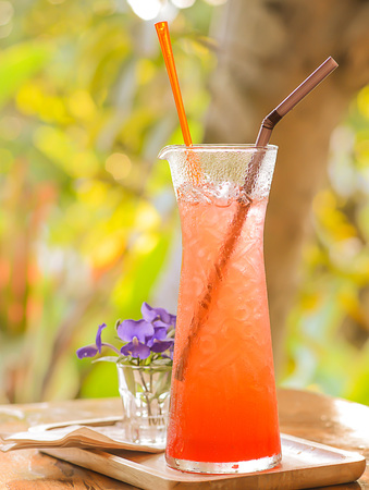 bokeh background: Strawberry Soda placed on wooden floor.focus glass,blurred background and poor light.