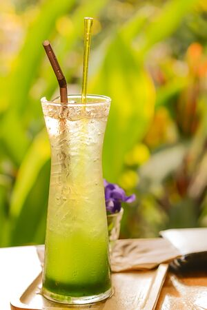 poor light: Kiwi Soda on wooden floor.focus grass,blurred background and poor light. Stock Photo