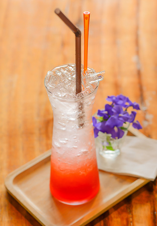 poor light: Strawberry Soda placed on wooden floor.focus glass,blurred background and poor light.
