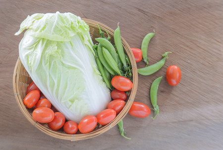 Tomato,Chinese cabbage,Sweet peas in Bamboo basket placed on wooden floor.