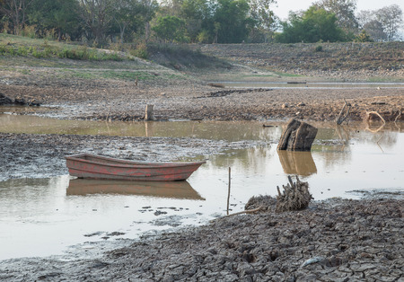 dry land: Cracked earth,Drought,Dry land,Red boat,Dry Dam.focus on boat.