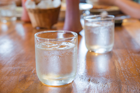 poor light: Glass water with ice on wooden table.Focus front glass,background blur and poor light.