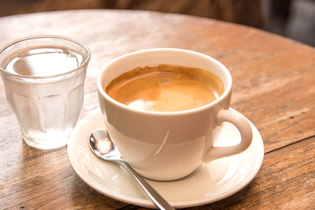 Coffee,White Coffee Mug,Glass water placed on wooden table.Focus coffee,soft focus background.