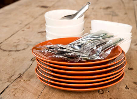 stackable: Dish dark brown many dishes stacked , fork , Cup white stackable on wooden table.