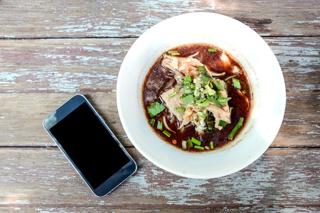thai noodle: Thai noodle in white Bowl , Black display Smart phone beside bowl noodles.All placed on wooden table.