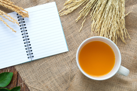 glass paper: Orange juice and sweetmeat with notebook and pen on Sackcloth brown.Top view focus.