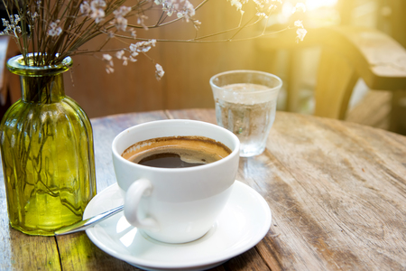 the backlighting: White coffee cup with dry flower and backlighting place on wooden table.Focus coffee. Stock Photo
