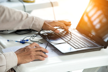 back lighting: Technician using laptop computer on white table with back lighting. Stock Photo