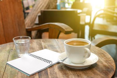 Café con el cuaderno y el vaso de agua en la tabla de madera Iluminación posterior. Foto de archivo
