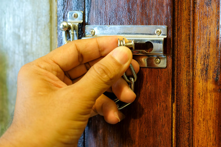 safety device: Security chain by hand safety device for the door. Stock Photo