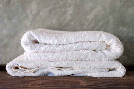 White towel placed on a wooden tray.concrete wall background.