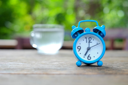 Seven oclock,Blue alarm clock on wooden with green blurred background.