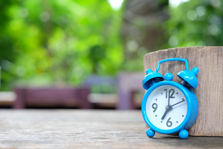 seven o'clock: Seven oclock,Blue alarm clock on wooden with green blurred background.